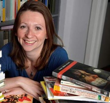 Ann Morgan, along with just some of the books she read in her project.  Photo by Darren Russell, via BBC Culture Web site